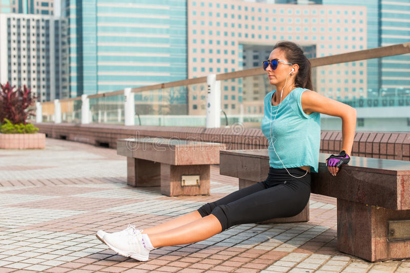 Fit woman doing triceps bench dips exercise while listening to music in headphones. Fitness girl working out in the city.  stock photos