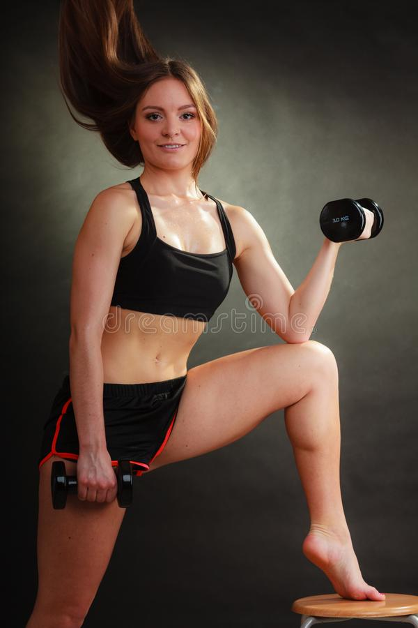 Fit woman exercising with dumbbells stock photos