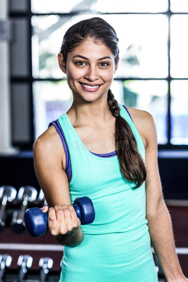 Fit woman exercising with dumbbells stock image