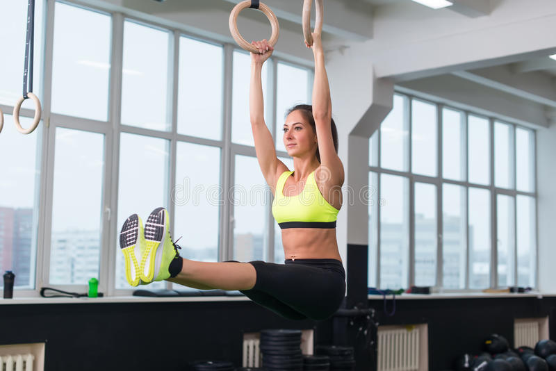 Fit woman exercising with gymnastic rings raising legs in gym. stock image