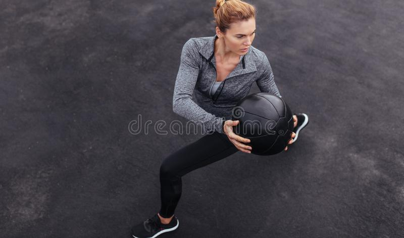 Fit woman exercising outdoors with medicine ball stock photo