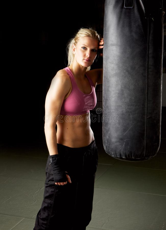 Fit Woman in Gym. Portrait of a cool fit woman in gym standing against a punching bag royalty free stock photography