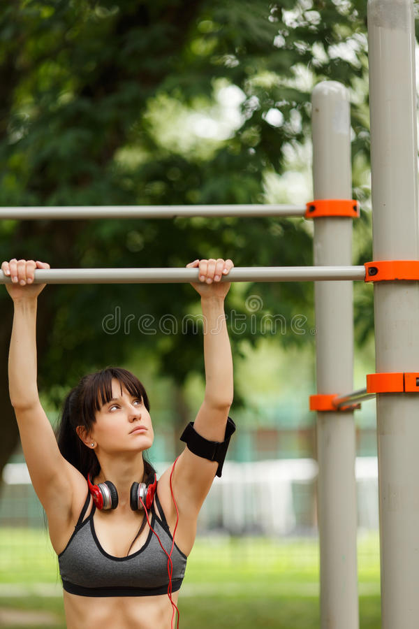 Fit woman with headphones preparing to do pull ups stock image