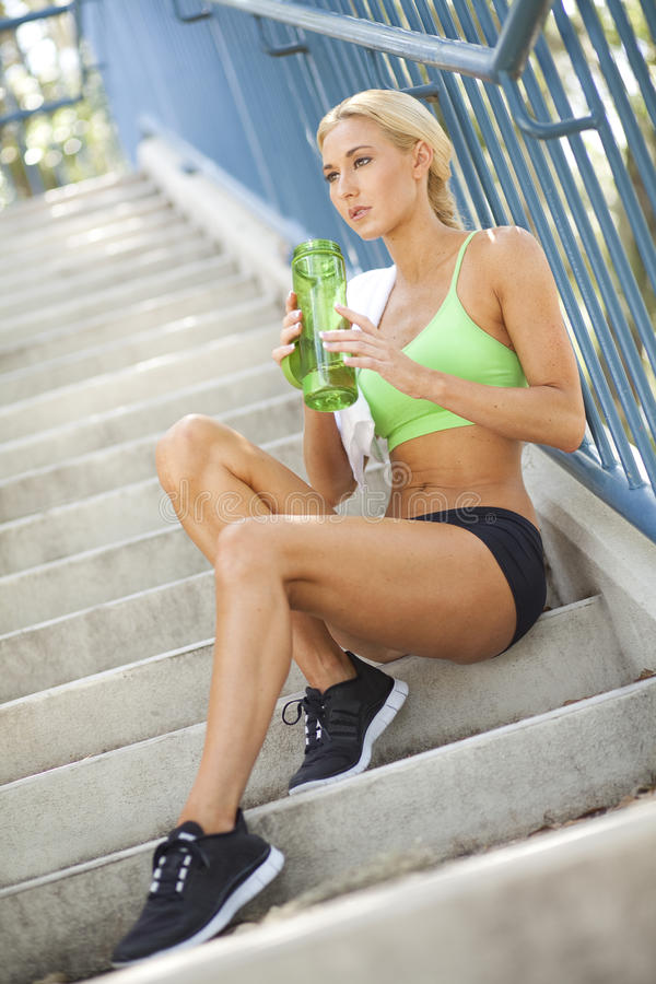 Fit woman holding sports bottle on steps. A fit, attractive female sitting on steps holding a sports bottle stock image