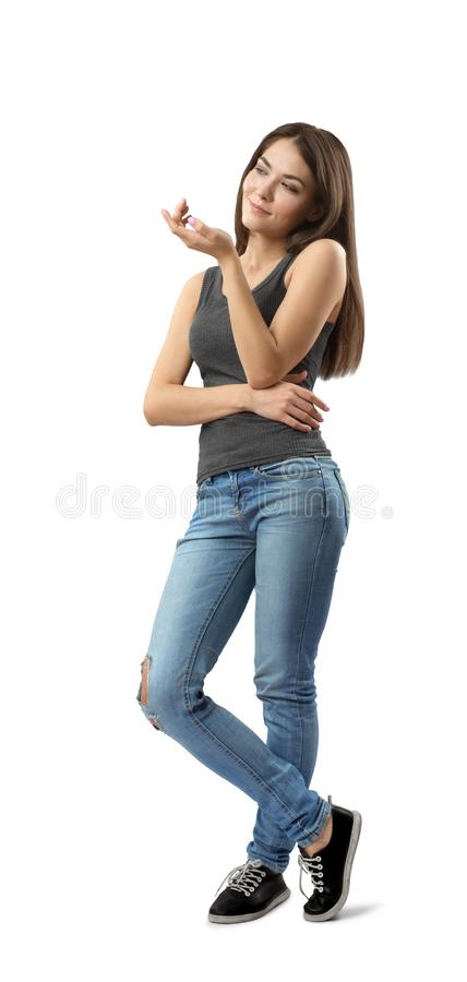 Fit woman in jeans and top standing in half-turn, head tilted to left, right arm across belly, left arm bent and raised. On white background. Inquisitive mind stock photography