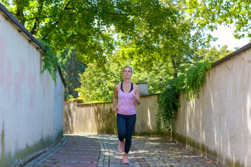 Fit woman jogging down a leafy shady lane. In summer approaching the camera full length in a health and fitness concept royalty free stock photos