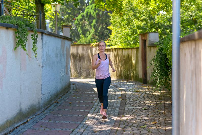 Fit woman jogging down a leafy shady lane. In summer approaching the camera full length in a health and fitness concept stock photography