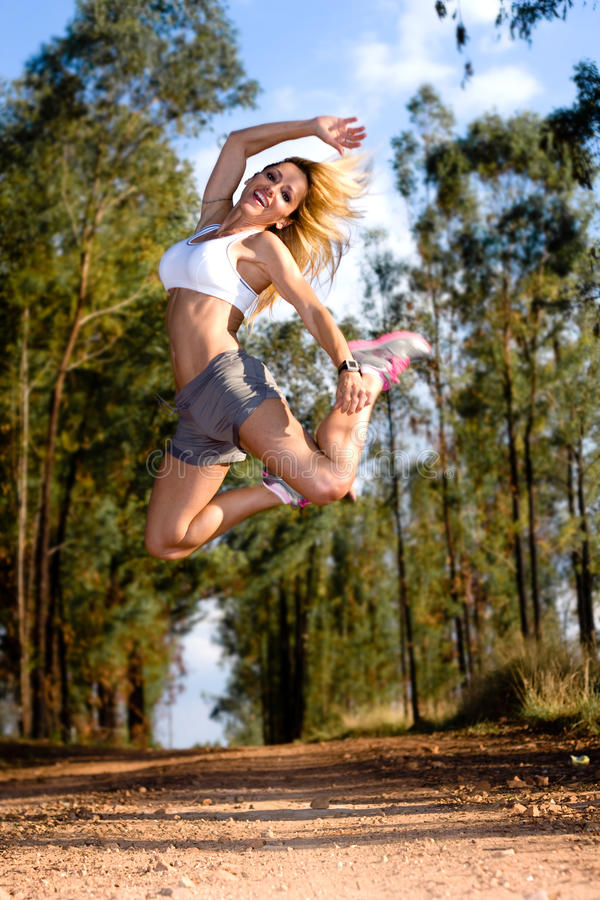 Fit woman jumping high stock photography