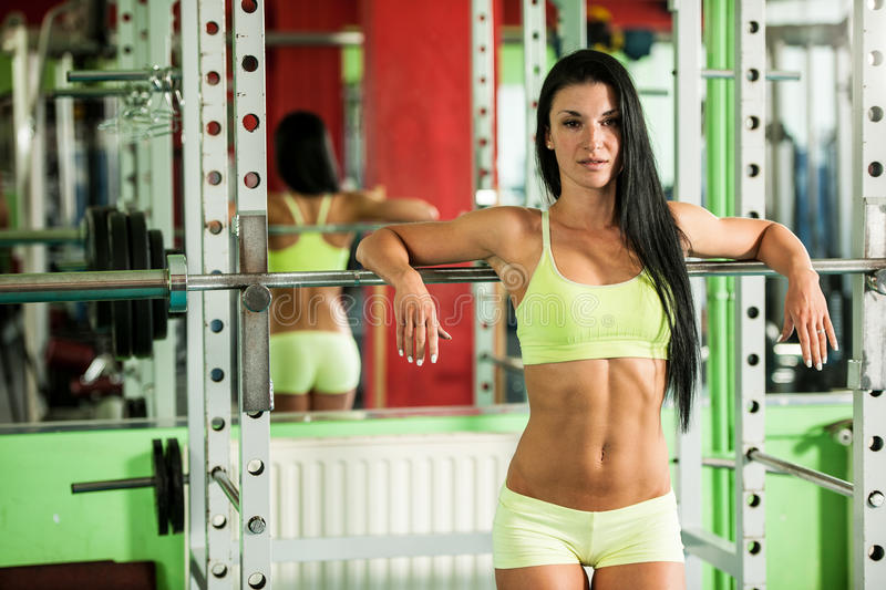 Fit woman leaning on weight bar resting after tough training in fitness gym stock image