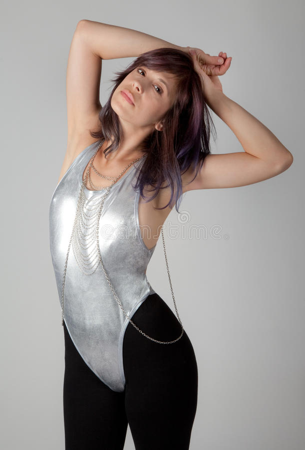 Fit Woman in Leotard and Leggings. An image of an attractive young woman wearing a shiny silver leotard over black leggings with a cross body chain stock photography