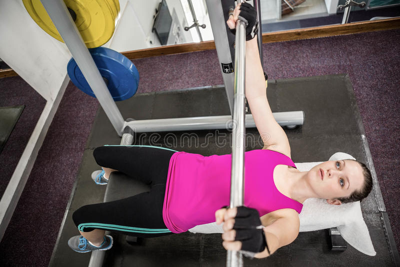 Fit woman lifting the barbell bench press stock image