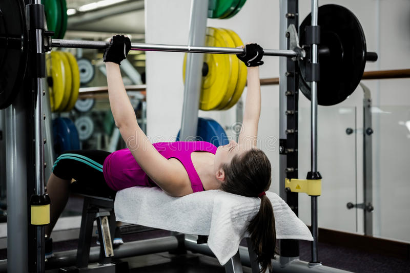 Fit woman lifting the barbell bench press royalty free stock images