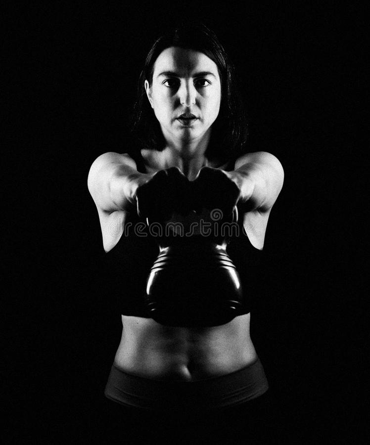 Fit woman lifting kettle bell. Fitwoman lifting kettle bell for shoulder workout stock photos