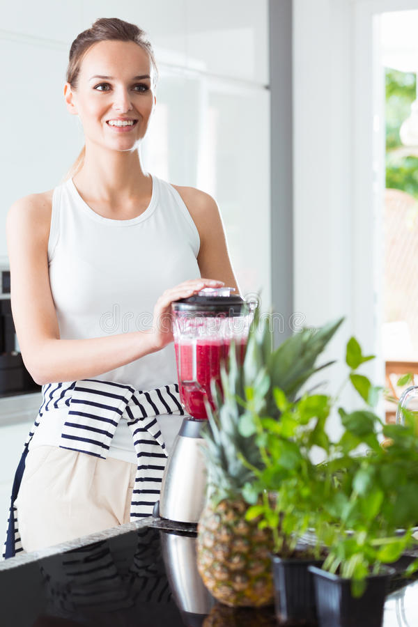 Fit woman making delicious smoothie royalty free stock photos