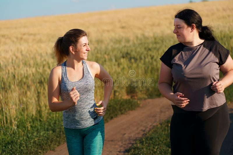 Fit woman motivate her friend at outdoor jogging. Young fit women supporting and motivate her friend at outdoor jogging. Friendship, group workout, weight losing royalty free stock photo