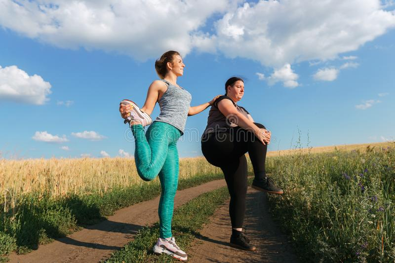 Fit woman motivate her friend at outdoor workout. Young fit women motivate her overweight friend at outdoor workout. Fitness, friendship, motivation concept royalty free stock photo