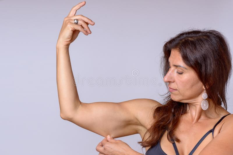 Fit woman pinching the skin of her upper arm. Fit muscular woman pinching the skin of her upper arm with her fingers as she shows of her toned physique in a stock photo