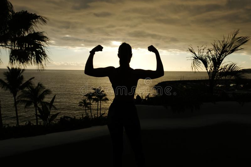 Fit woman posing silhouette with sunset over the ocean stock image