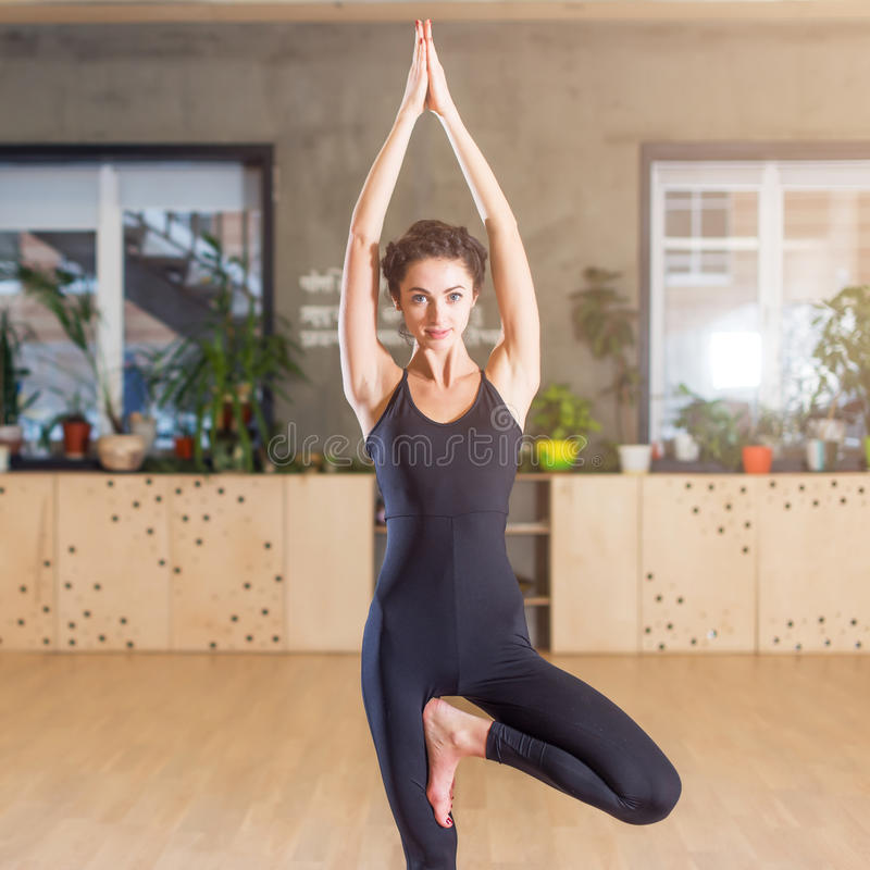 Fit woman practicing yoga exercise called Tree Pose standing on one leg indoors stock photo