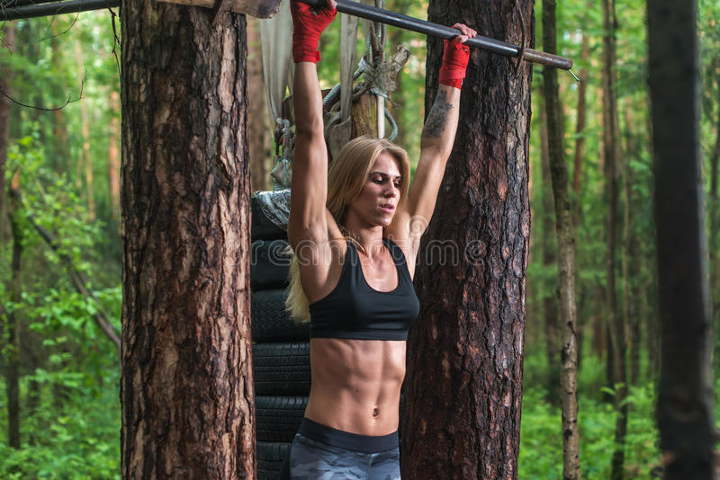 Fit woman preparing to do pull ups on horizontal bar. royalty free stock image