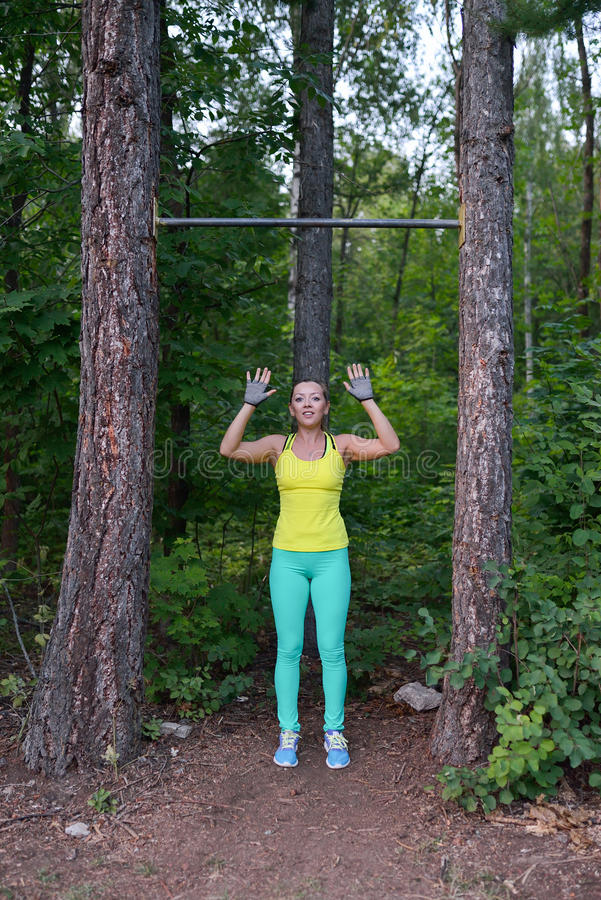 Fit woman preparing to do pull ups on horizontal bar royalty free stock photo