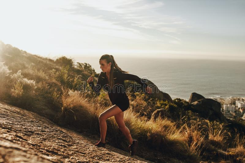 Fit woman running up a rocky mountain trail royalty free stock image