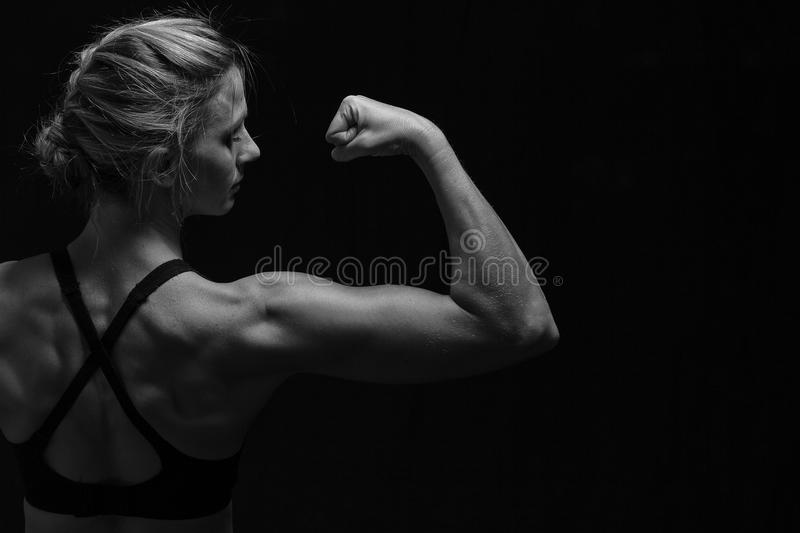 Fit woman with shaped muscles on back in artistic conversion. Fit woman with shaped muscles on her back in artistic conversion royalty free stock image