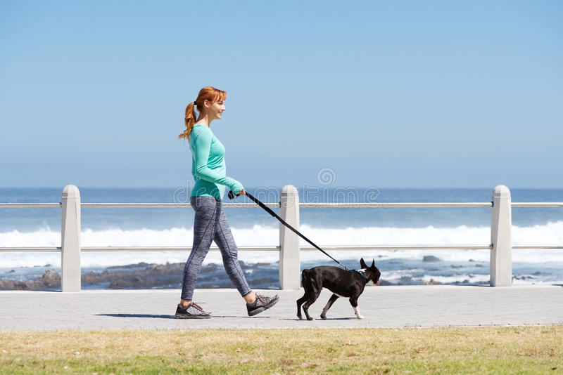 Fit woman smiling and walking dog on path by sea. Full body portrait of fit woman smiling and walking dog on path by sea royalty free stock photo