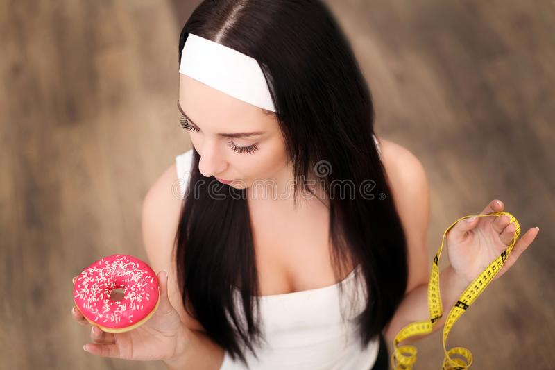 Fit woman in sport clothing holding measuring tape while eating. A donut again stock image