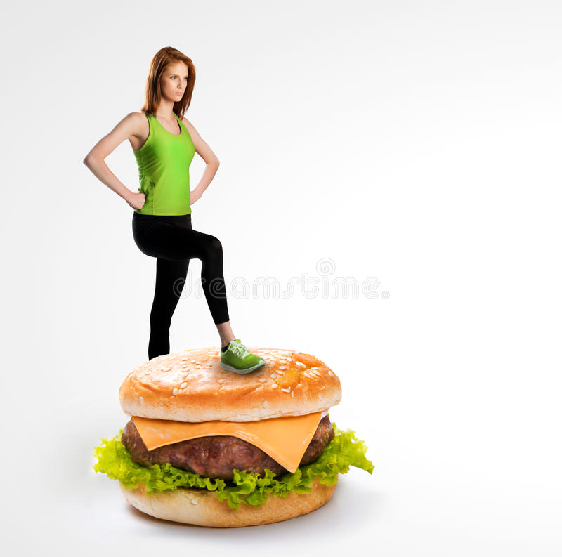 Fit woman standing on a cheeseburger. Fit concept stock photography