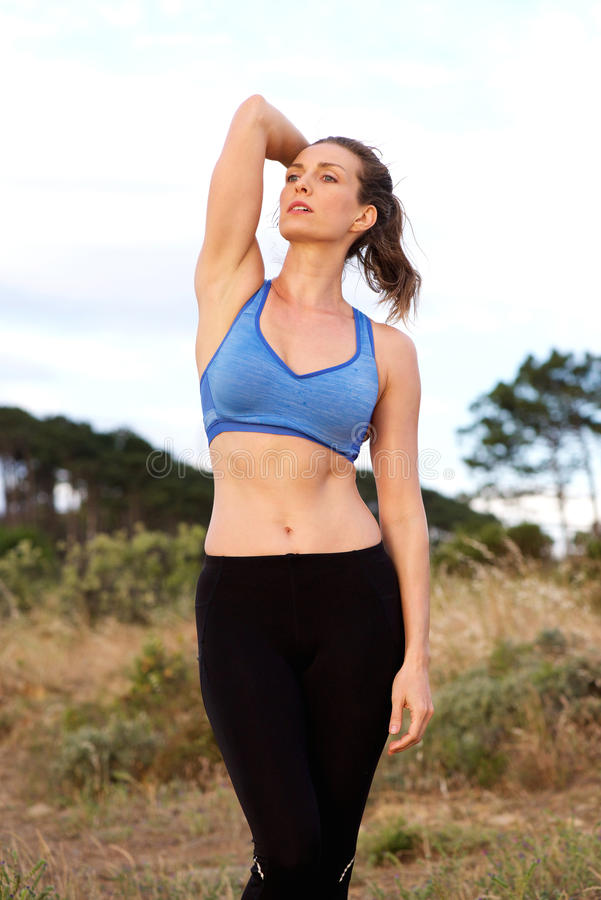 Fit woman standing outside with hand in hair stock photos