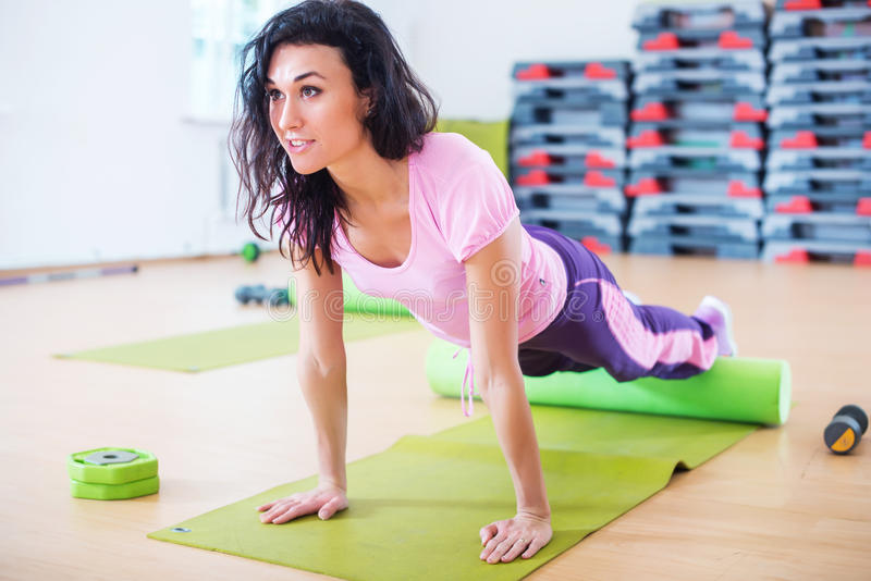 Fit woman stretching on floor using foam roller doing plank exercise, push ups stock photos