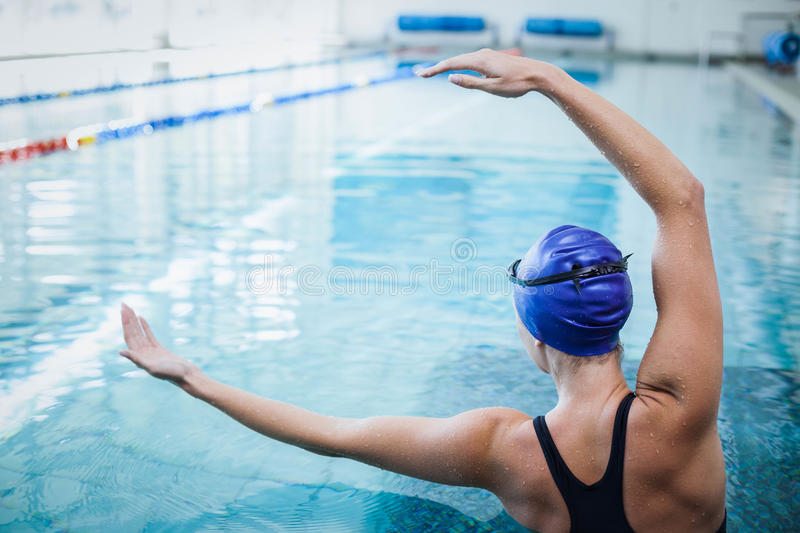 Fit woman stretching her arms in the water royalty free stock photography