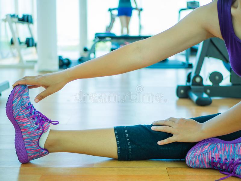 Fit woman stretching her leg to warm up in gym room stock photo