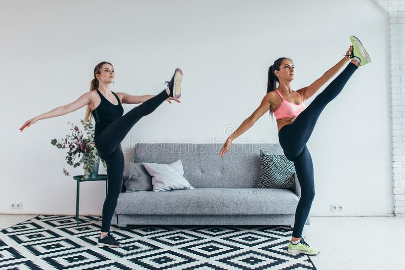 Fit woman stretching legs warming up workout at home. Fit women stretching legs warming up workout at home royalty free stock photos