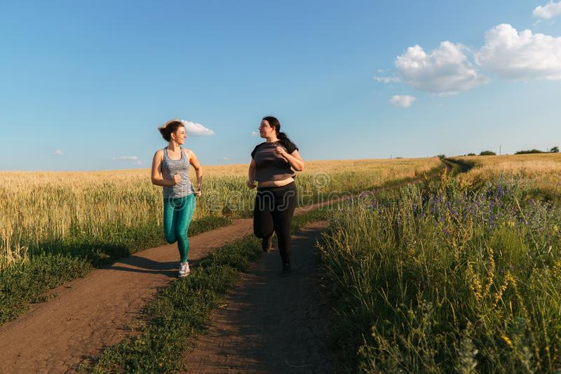 Fit woman support and motivate friend at workout. Young fit women support and motivate her overweight female friend at outdoor jogging. Friendship, personal royalty free stock photos