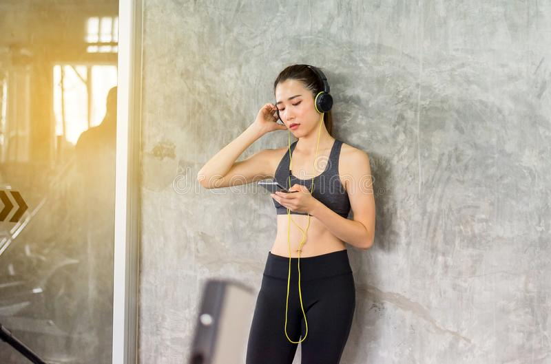 Fit woman using headphone and listening to music while relax after the training session in gym,Concept healthy and lifestyle,Femal. E taking a break after royalty free stock photos