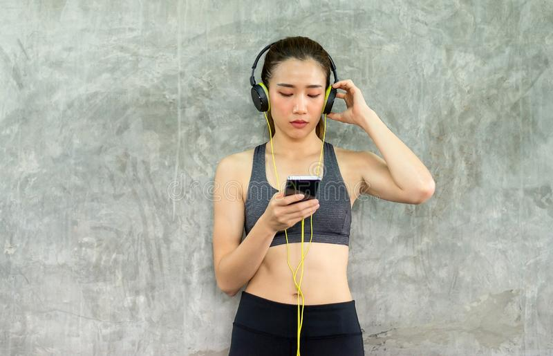 Fit women using smart phone connection internet with headphone and listening to music while sitting with relax after the training. Fit woman using smart phone stock image