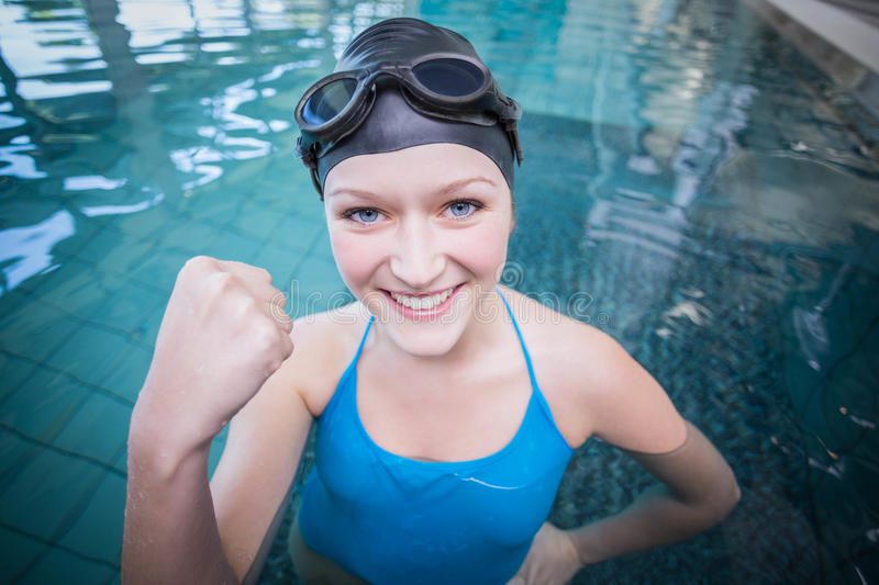 Fit woman wearing swim cap and goggles with raised fist. In the pool stock images