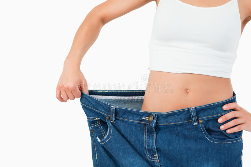 Fit woman wearing too large jeans stock photos