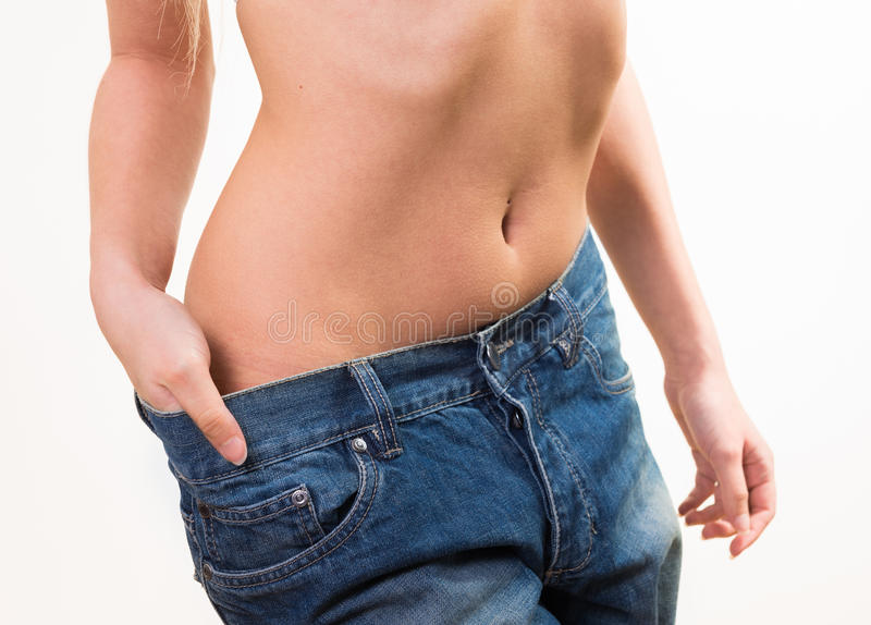 Fit woman wearing too large pants royalty free stock photo