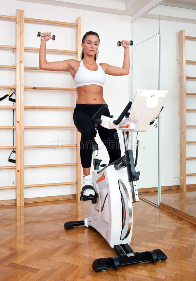 Download Fit Woman Working Out On Stationary Bicycle Stock Image - Image: 19772775