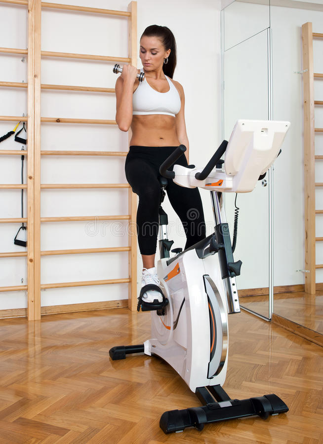 Download Fit Woman Working Out On Stationary Bicycle Stock Photo - Image of muscle, shape: 19772776