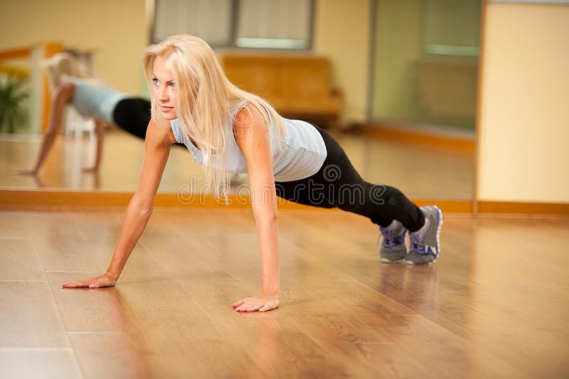 Fit woman works out in gym making push ups stock image