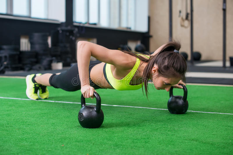 Fit woman young doing push ups exercise with dumbbells in the gym stock photography