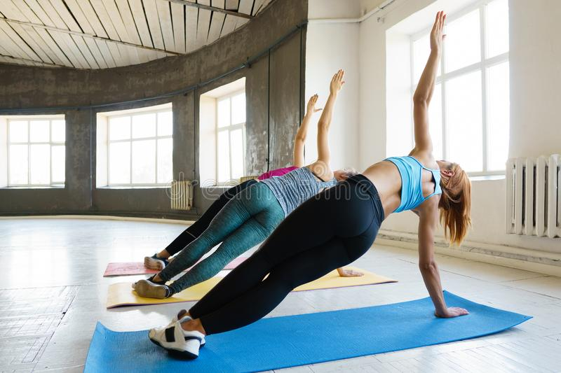 Fit women doing side plank in gym, back view royalty free stock image