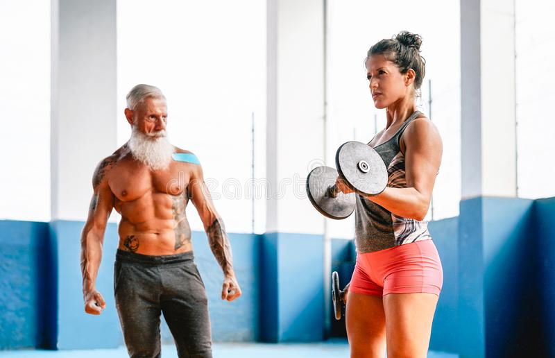 Fit woman making curl biceps exercise with dumbbells in fitness gym center - Female athlete training with her personal trainer stock photo