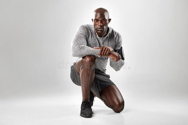 Fit young african man kneeling on grey background. Portrait of fit young african man kneeling on grey background and looking at camera stock photos