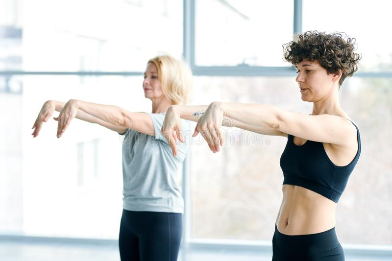 Fitness for hands. Fit young and aged women keeping their wrists down while stretching arms forward during one of exercises stock images