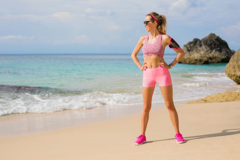 Fit athletic woman standing on the beach ready for workout. Fit, young and athletic woman standing on the beach ready for workout royalty free stock images